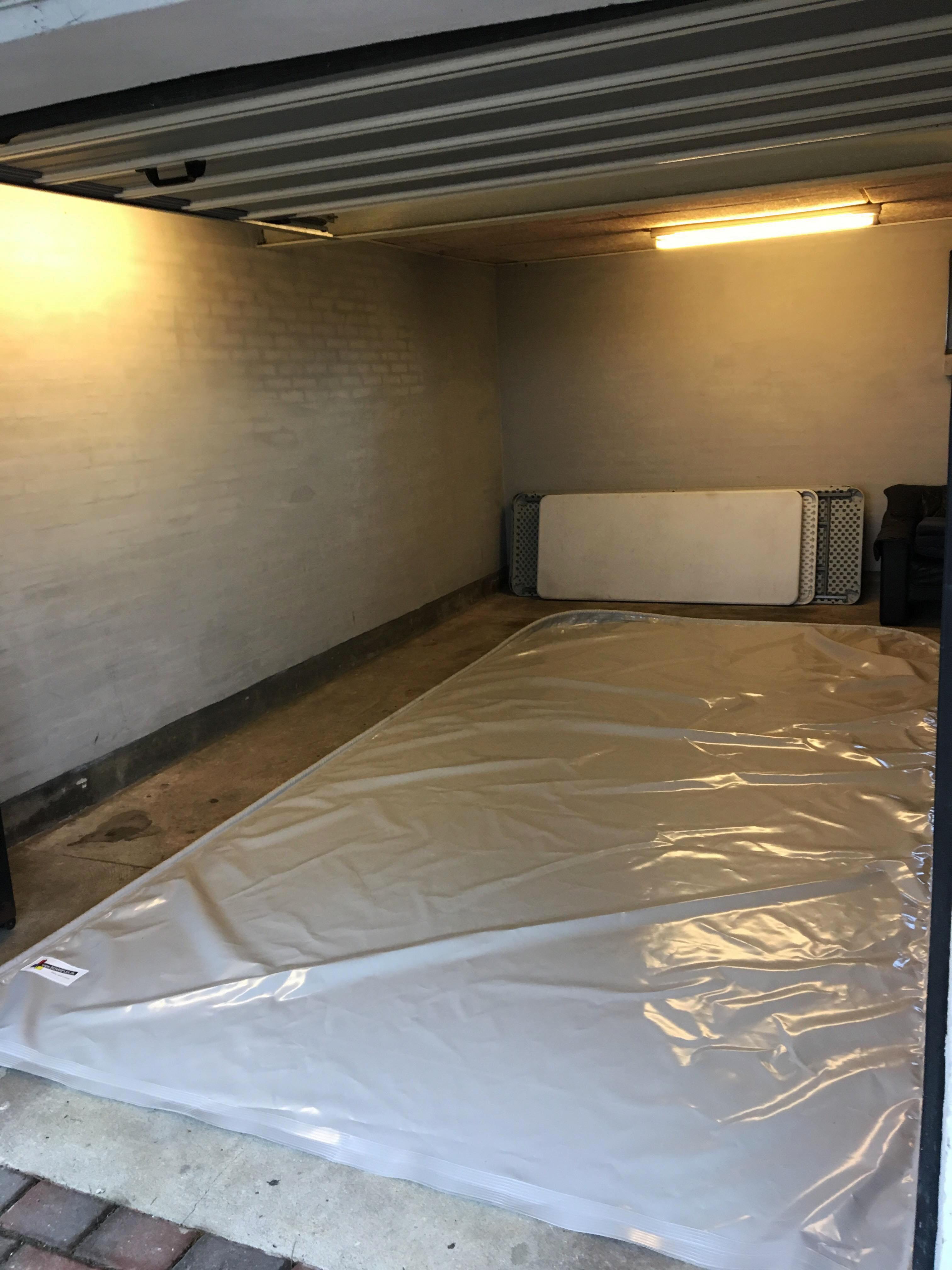 Åben garage med spildunderlag til bil